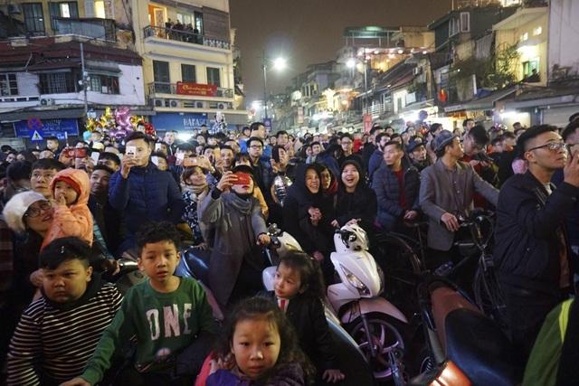Hàng nghìn người dân có mặt thích thú hò reo theo những vệt sáng trên không trung.