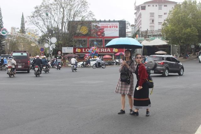 Hai thiếu nữ đội mưa dạo phố Đà Lạt