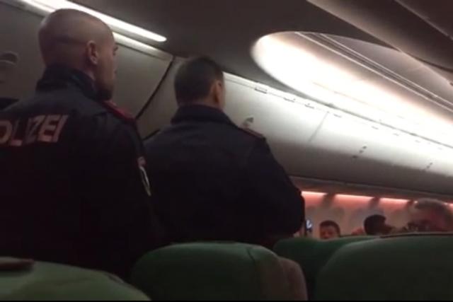 Cảnh sát lên máy bay áp giải những hành khách xô xát xuống máy bay. (Ảnh: Mirror)