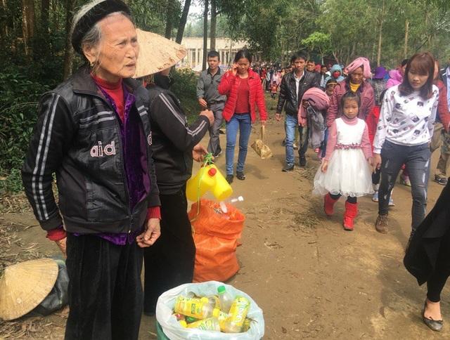 Cụ bà tranh thủ lấy chai lọ đến chùa bán cho người dân và du khách có nhu cầu mua để xin nước thánh.