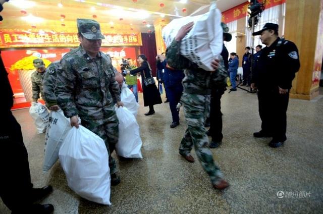 Nhân viên bảo vệ của Fangda vận chuyển từng bao tải tiền thưởng tết. (Ảnh: SCMP)