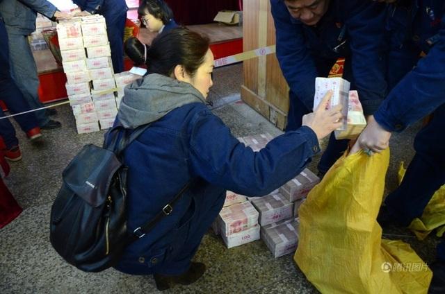 Một nhân viên công ty xếp từng cọc tiền thưởng tết vào bao tải. (Ảnh: SCMP)