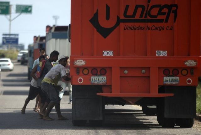 Những người đàn ông đang cố cướp gạo từ một chiếc xe tải chở lương thực trên đường đến cảng Puerto Cabello, Venezuela. (Nguồn: AP/REX/Shutterstock)
