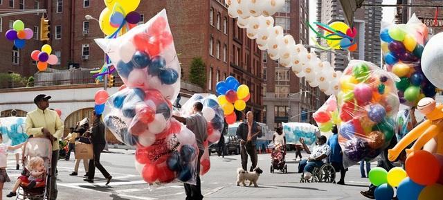 """Bức """"Caretaker"""" (Người chăm sóc) và những chùm bóng bay thắp sáng đường phố."""