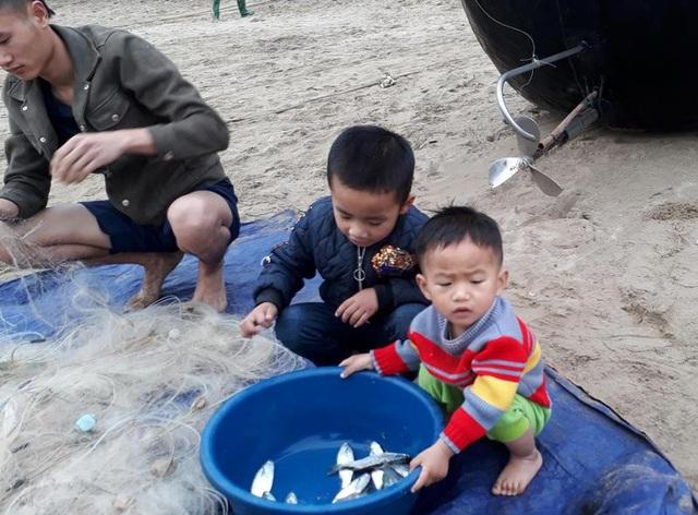 Những đứa trẻ theo bố mẹ ra bờ biển gỡ lưới