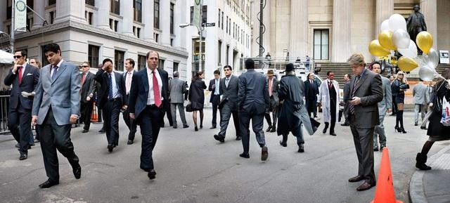 """Bức """"Hommage A Ellis"""" được chụp gần Phố Wall - trung tâm tài chính lớn của thế giới. Bức ảnh được chụp vào ngày Halloween hồi năm 2008, giữa những người đàn ông ăn mặc rất chỉnh chu, có một người đàn ông hóa trang thành kẻ sát nhân tâm thần. Bạn có thể tìm ra nhân vật ấy?"""