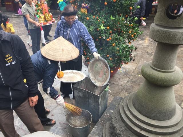 Hai cụ bà luôn tục rút hương du khách thắp dúng vào xô nước cho đỡ khói