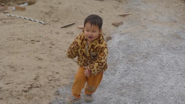 Cậu bé Trọng phấn khởi chạy tung tăng từ ngoài cổng vào.