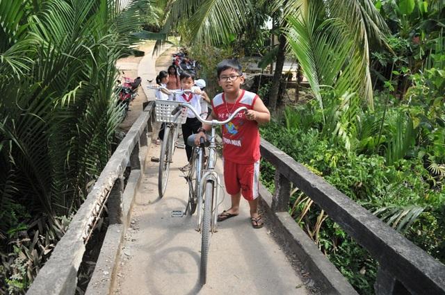 Mặt cầu nhỏ, dốc cao nên các em học sinh đi xe đạp phải dẫn bộ qua cầu...