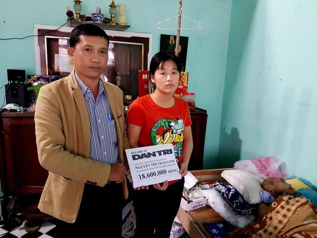 Đại diện lãnh đạo thị trấn Hà Lam trao quà của bạn đọc đến em Linh