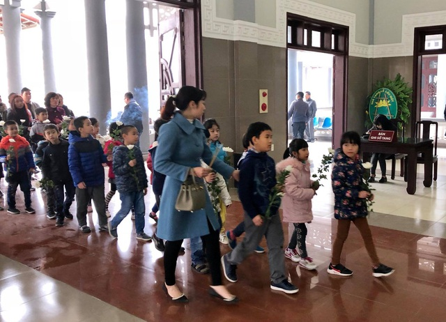 Các bạn lớp 2A6 trường tiểu học Tân Mai (Hà Nội), cầm những đoá hoa cúc màu trắng tới viếng bạn Hải An, cô bé hiến giác mạc sau khi qua đời vì bệnh u não cực kỳ hiếm gặp.