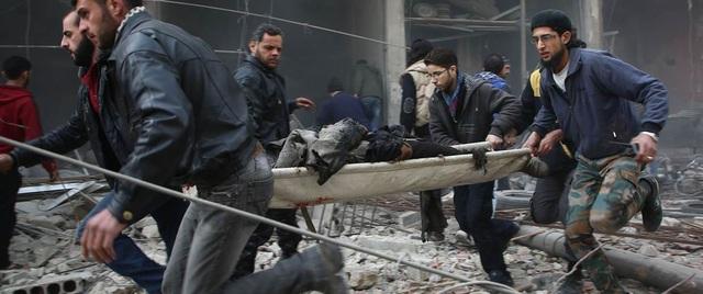 Lực lượng cứu hộ khiêng một người bị thương sau cuộc tấn công tại khu vực do phiến quân kiểm soát ở Kafr Batna, Syria ngày 6/2 (Ảnh: AFP)