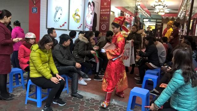 Đến gần trưa, mưa ngày càng nặng hạt, người dân vẫn xếp hàng chờ đến lượt. Người người xếp ghế ngồi đợi đến lượt mua vàng tại Bảo Tín Minh Châu