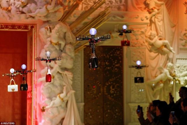 """Những chiếc """"drones"""" được sử dụng để giới thiệu những mẫu túi xách mới của thương hiệu thời trang. Sang phần trình diễn trang phục, các người mẫu sẽ bước lên sàn catwalk."""