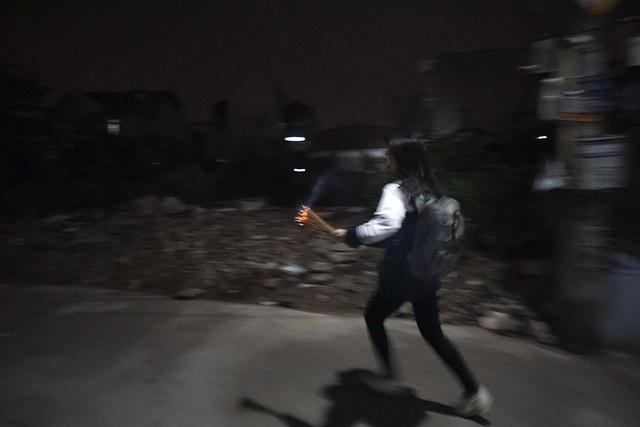 Một học sinh đang lấy lửa mang về nhà.