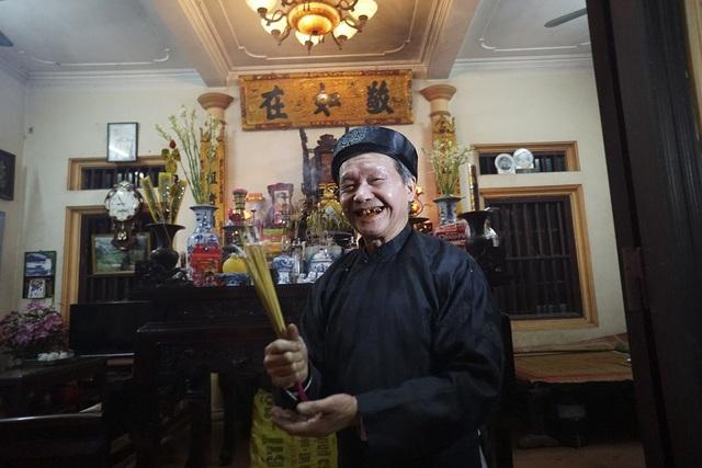 Ông Lê Văn Khuê vừa đỡ bó hương từ tay người vợ đi lấy lửa ở đình làng mang về nhà trong sự phấn khởi.