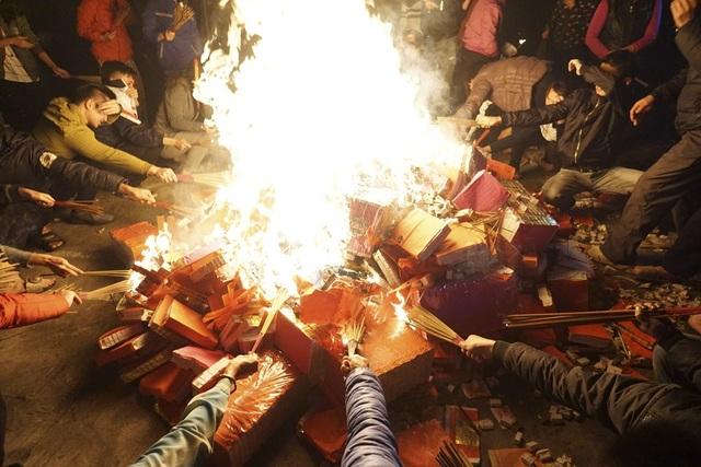 Ngọn lửa bùng lên đốt cháy vàng mã, người dân bắt đầu vào lấy lửa từ đây.