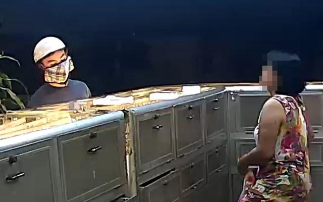 Tên cướp đội mũ bảo hiểm, đeo khẩu trang che kín mặt tiến vào vào tiệm vàng, uy hiếp bà chủ.