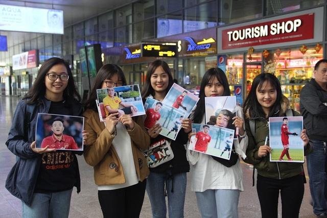 Các cổ động viên nữ mang theo những tấm hình của các cầu thủ mà mình hâm mộ để đón chào họ trở về