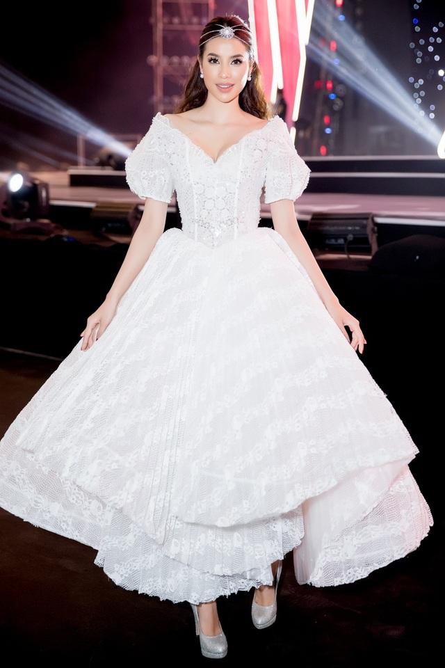 Nếu như Hoa hậu H'hen Niê đầy nữ quyền trong bộ vest đen thì Hoa hậu Phạm Hương lại xinh đẹp như nàng công chúa trong trang phục với kiểu dáng cổ thuyền xẻ sâu kết hợp phần thân dưới xếp lớp bồng bềnh.