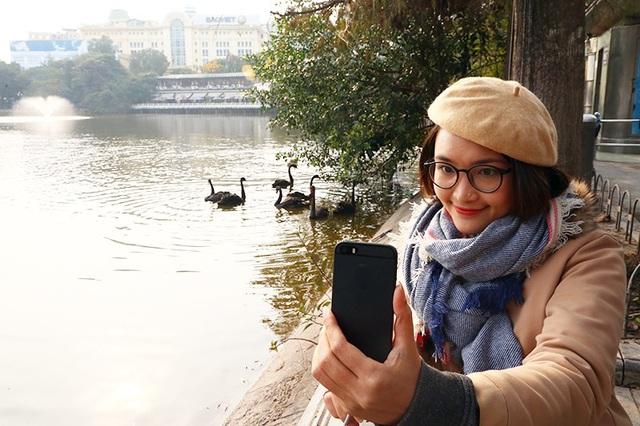 Một bạn trẻ may mắn lựa chọn được vị trí đẹp để selfie với đàn thiên nga
