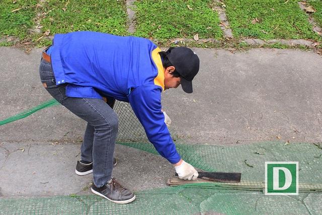 Công nhân cắt lưới để tiến hành quây nhốt đàn chim thiên nga ra giữa hồ, tránh việc bị mất trộm và dễ quản lý (Ảnh: Trần Thanh).