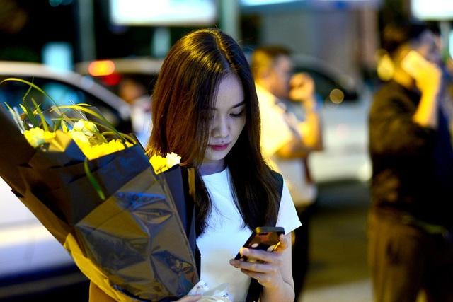 Cô gái ôm bó hoa tươi đứng chờ đợi.