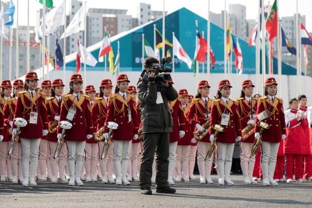 Trong bộ đồng phục áo đỏ, quần trắng và đi bốt cao, đội cổ động Triều Tiên đã trở thành tâm điểm chú ý của các phóng viên, các vận động viên và đặc biệt là khán giả của nước chủ nhà tại Làng Olympic. (Ảnh: AFP)
