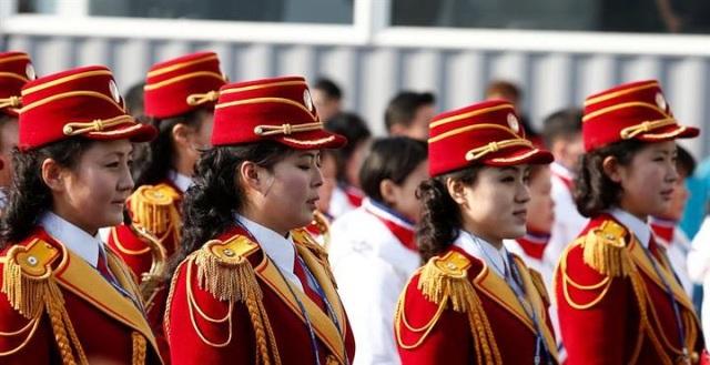 Các cô gái Triều Tiên đã trình diễn kỹ năng vừa di chuyển, vừa xếp đội hình trong khi vẫn có thể chơi các loại nhạc cụ như kèn, trống tại lễ thượng cờ ở Làng Olympic. (Ảnh: EPA)