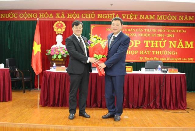 Ông Nguyễn Xuân Phi, Ủy viên Ban Thường vụ Tỉnh ủy, Bí thư Thành ủy, Chủ tịch HĐND TP Thanh Hóa tặng hoa chúc mừng ông Lê Anh Xuân (bìa phải)