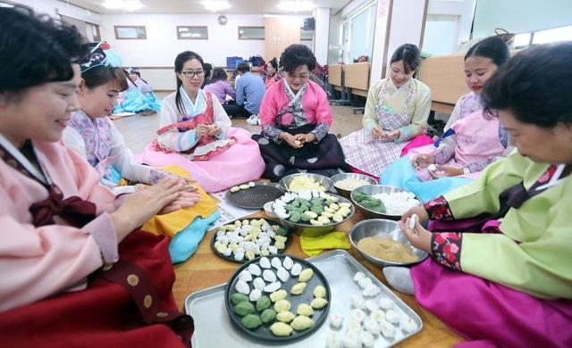 Các tình nguyện viên Hàn Quốc hướng dẫn các cô dâu nước ngoài cách làm bánh tại lễ hội Chuseok ở tỉnh Gangwon, Hàn Quốc. (Ảnh: Yonhap)