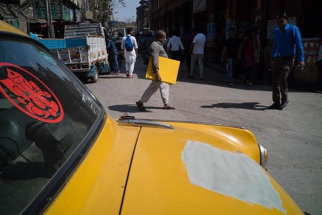Chiếc xe bị mất một mảng sơn và người phụ nữ đang cầm trên tay một tấm gỗ cùng màu, trông cứ như vừa giật ra vậy.