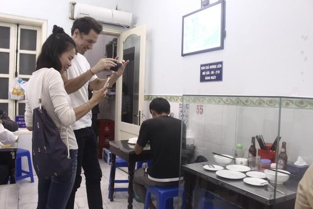 Thực khách nước ngoài thích thú chụp ảnh bộ bàn ghế ông Obama từng ngồi. (Ảnh: Hồng Vân)