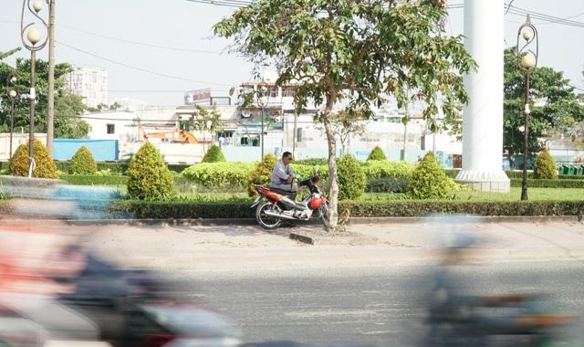 Một tài xế xe ôm núp mình dưới bóng cây để chờ khách
