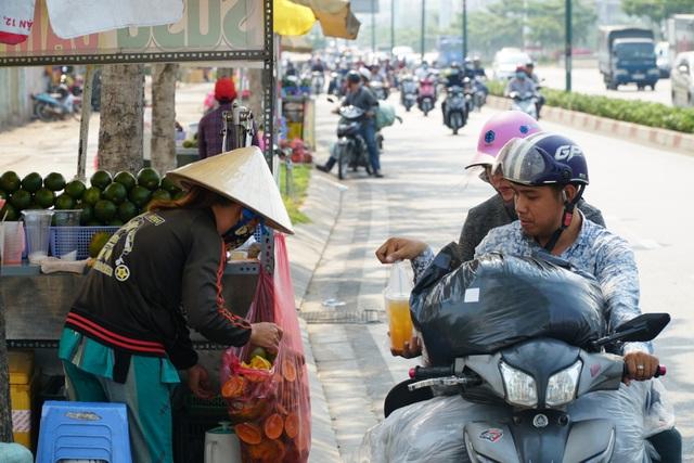 Hai vợ chồng chở hàng về Thủ Đức tranh thủ ghé vào ven đường mua 2 ly nước cam với giá 10 ngàn đồng/ly.