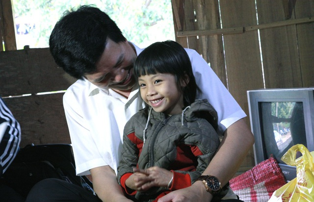 Bí thư Huyện ủy Con Cuông ân cần thăm hỏi bé Trúc Linh trong lần trở lại thăm cháu cùng PV Dân trí.