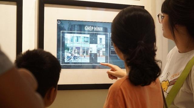 Du khách chơi ghép hình. Những hình ảnh trong trò chơi gắn liền với chủ đề của triển lãm
