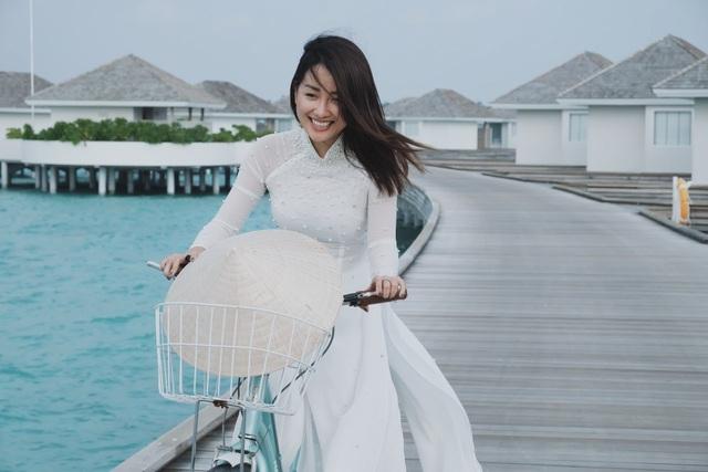 """Không chỉ khoe dáng với bikini, đầm xẻ sâu, Quỳnh Chi còn gây ấn tượng với concept áo dài trắng, nón lá Việt Nam giữa biển xanh cát trắng của """"thiên đường du lịch""""."""
