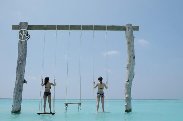 Trước khung cảnh biển xanh ngắt, nước trong vắt và nắng vàng rực rỡ, đôi bạn đã không khỏi thích thú. Cả hai cùng khoe dáng trong những bộ bikini gợi cảm. Quỳnh Chi chia sẻ: Cuộc hành trình tới Maldives không hề dễ dàng vì không có chuyến bay thẳng từ Hà Nội tới Male (thủ đô của Maldives). Nhưng cũng giản tiện được khâu xin visa. Tới Maldives các bạn sẽ được cấp visa tại chỗ, dấu visa ở đây cũng xinh đẹp hơn những đất nước khác. Nếu mọi người ở TP HCM có thể chọn chuyến bay transit ở Singapore, sau đó từ Sing bay thẳng tới Male. Còn ở Hà Nội thì bọn mình đã mua vé transit tại Bangkok, Thái Lan. Sau đó từ sân bay Suvarnabuhmi của Thái Lan di chuyển tới Male mất 4 giờ đồng hồ. Giá vé ở thời điểm bọn mình mua vào khoảng hơn 17 triệu cho 1 người.