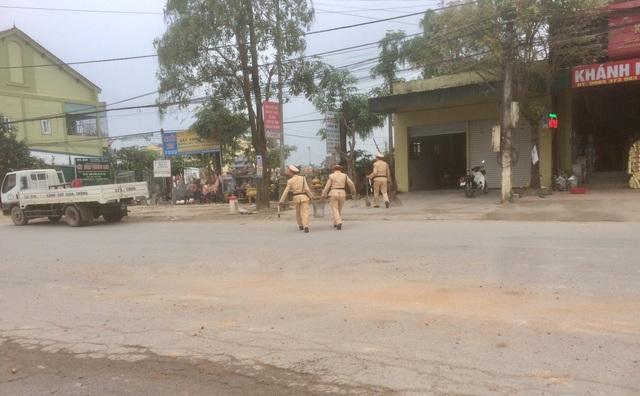 Ba cán bộ CSGT dừng xe bên đường quét dọn đất vương vãi.