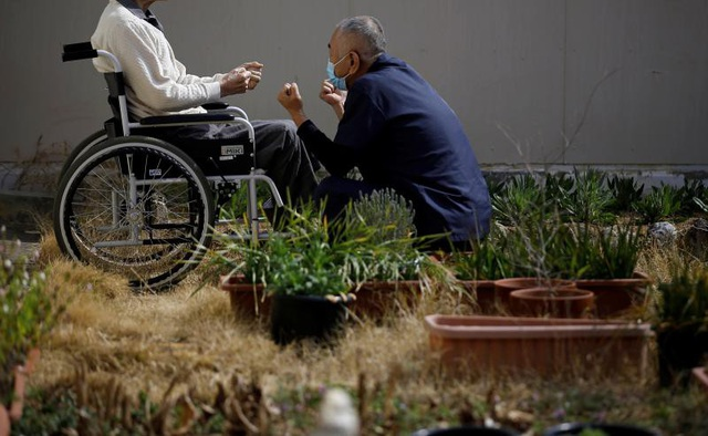 Một nhân viên nhà tù chăm sóc một tù nhân lớn tuổi. (Ảnh: Reuters)