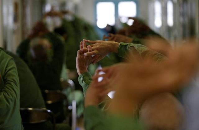 Các tù nhân lớn tuổi tập thể dục trong sảnh nhà tù. (Ảnh: Reuters)