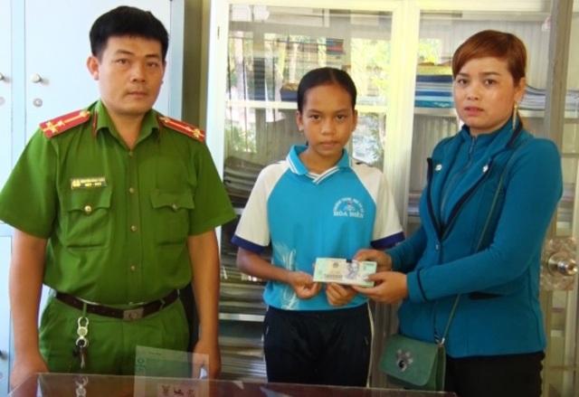 Đại diện công an xã Thuận Yên cùng em Huỳnh Thị Bích Trâm trao lại số tiền 37 triệu đồng cho chị Châu Thị Sành. (Ảnh: Anh Tuấn)