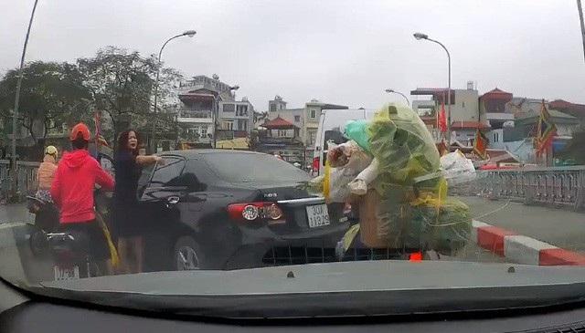 Nữ tài xế đi ô tô chỉ tay, đôi co với người đi xe máy ngay trên khu vực cầu đang đông đúc dòng phương tiện qua lại. (Ảnh cắt từ clip)
