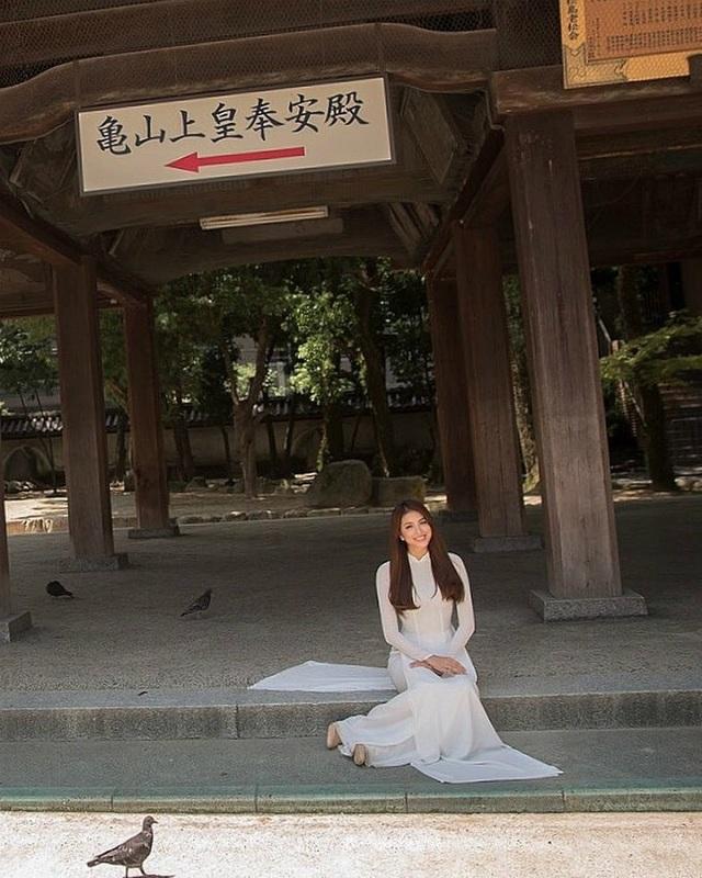 Hoa hậu Phạm Hương diện áo dài trắng dịu dàng khi ngồi chụp ảnh trước cửa một ngôi đền.