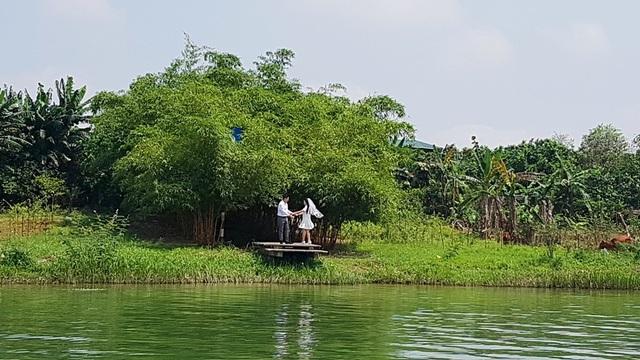 Một cặp đôi chụp ảnh cưới bên bờ sông thơ mộng