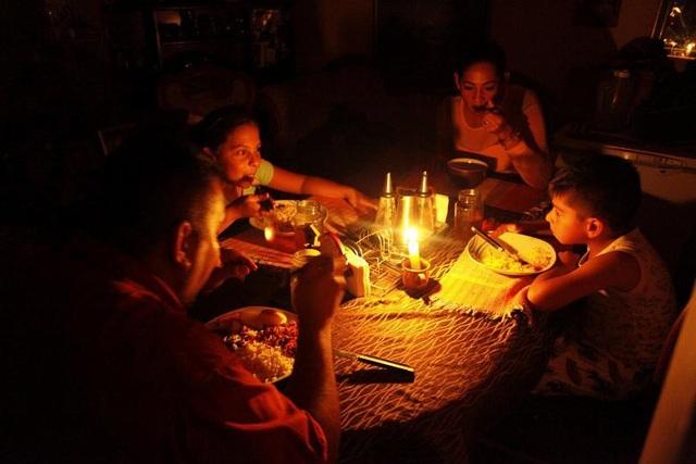 Hạn hán đã khiến mực nước trong các đập và hồ thủy điện quan trọng tại 6 bang ở phía tây Venezuela giảm và đẩy nước này vào cuộc khủng hoảng năng lượng mới. Sản lượng điện giảm dẫn tới việc Venezuela phải cắt điện và phân chia sử dụng theo từng khu vực. Trong ảnh: Gia đình cô Lisney Albornoz (thứ 2 từ phải sang) thắp nến để ăn tối khi thành phố San Cristobal cắt điện luân phiên vào ngày 14/3.