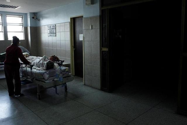 Bênh nhân nằm ở hành lang bệnh viện trung tâm San Cristobal chờ có điện để chạy thang máy. Cuộc khủng hoảng kinh tế kéo dài đã ảnh hưởng tới việc đầu tư, sửa chữa các hạng mục cơ sở hạ tầng xuống cấp ở Venezuela, trong đó có mạng lưới điện. Hiện tại, tình hình trở nên tồi tệ hơn nữa khi lượng mưa ở phía tây nước này ngày càng giảm.