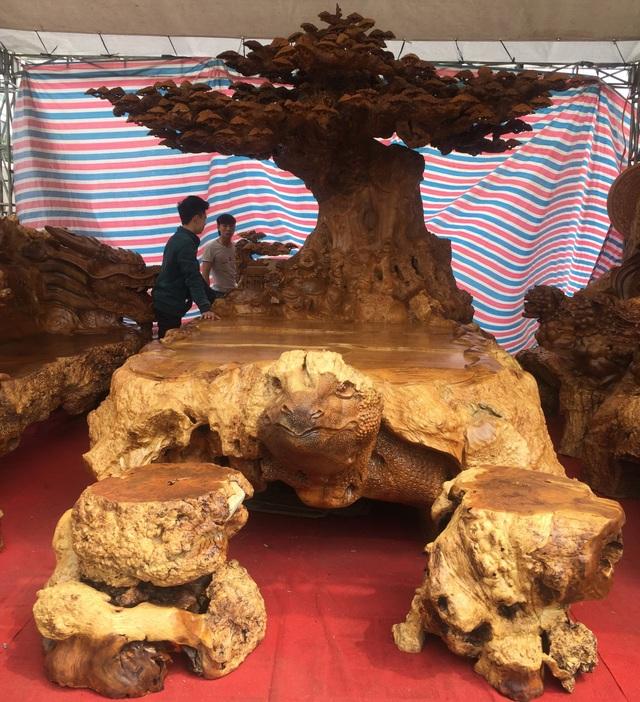 Bàn nguyên khối bằng gỗ nu đinh hàng nghìn năm tuổi, dài 4m, đỉnh tán cây tùng cao 3,2m, rộng 1,8m, được chạm khắc cầu kỳ, tinh xảo, đầu bàn được chạm hình đầu rùa