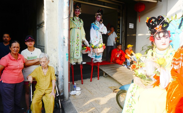 2 tiên nữ phải nhờ hiên nhà dân trong lúc chờ đoàn diễu hành.